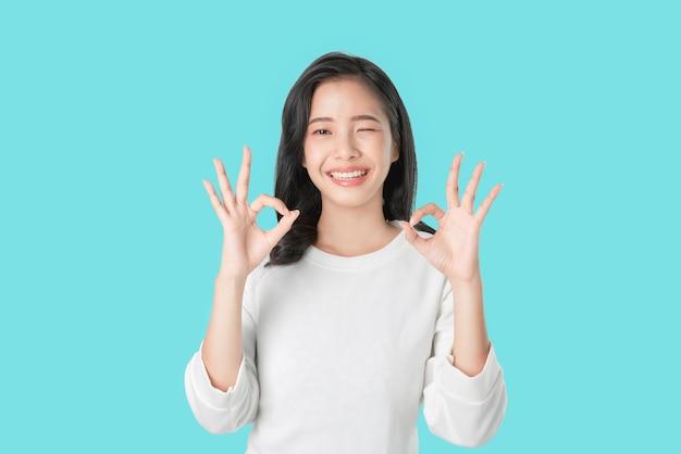 La donna felicemente asiatica del ritratto mostra il segno e sorridere giusti
