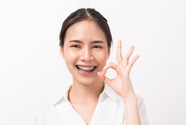 La donna felicemente asiatica del ritratto mostra il segno giusto e le parentesi graffe che sorridono sulla parete bianca,