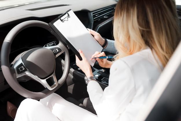 La donna firma un accordo con un concessionario di automobili