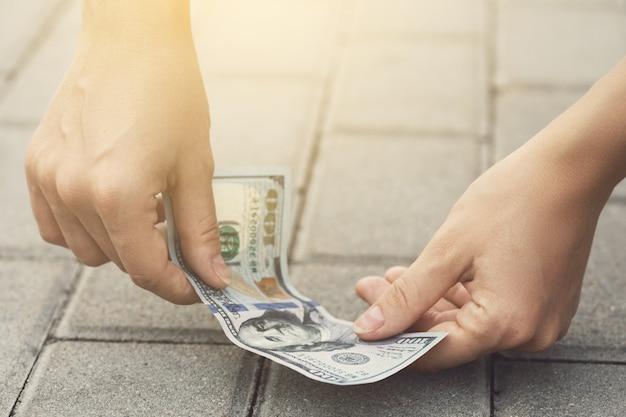 La donna fortunata sta raccogliendo un centinaio di dollari da terra.