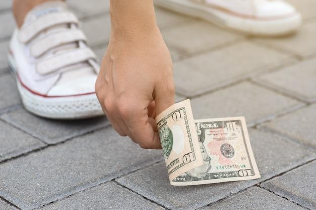 La donna fortunata sta raccogliendo una banconota da dieci dollari da terra.