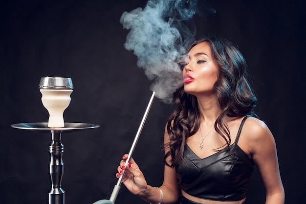 La donna fuma narghilè / bella donna affascinante in abito nero fuma un narghilè