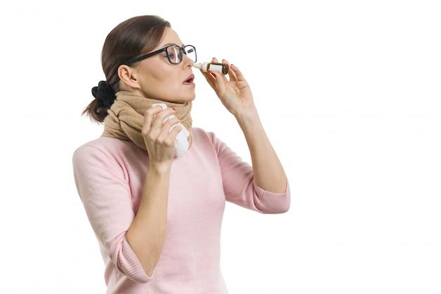 La donna gocciola gocce per il naso. bianco, isolato