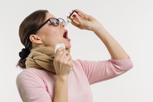 La donna gocciola gocce per il naso
