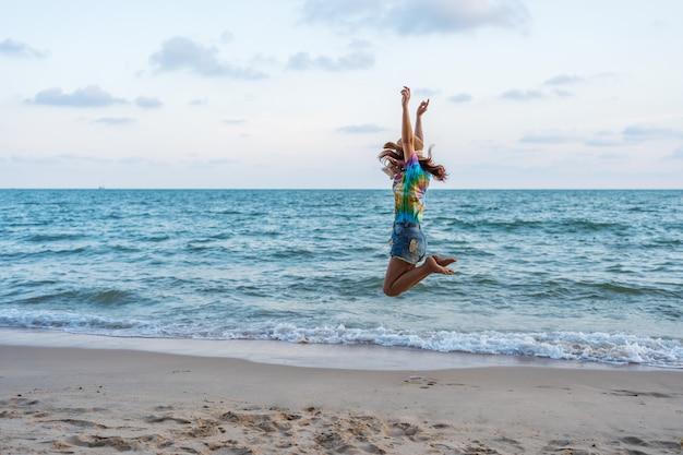 La donna gode e saltando sulla spiaggia del mare