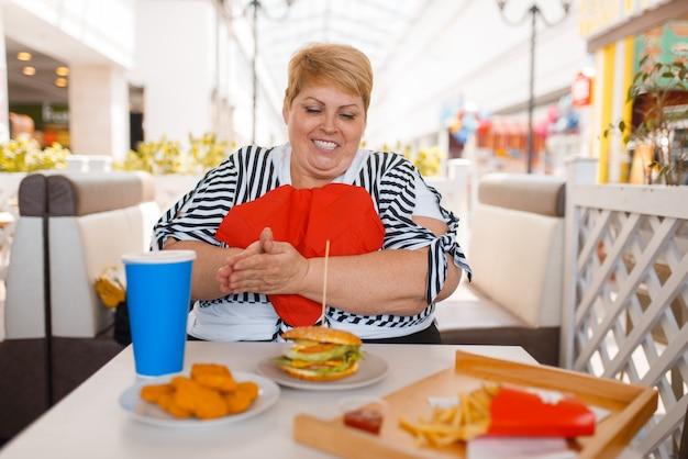 La donna grassa si prepara a mangiare un fast food nella food court del centro commerciale. persona di sesso femminile in sovrappeso al tavolo con pranzo spazzatura