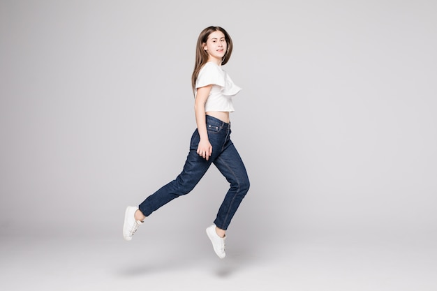La donna graziosa celebra saltando e incoraggiando isolato sulla parete bianca