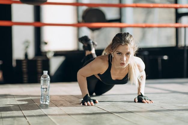La donna graziosa che esamina la macchina fotografica mentre fa spinge aumenta dal pavimento di legno in palestra