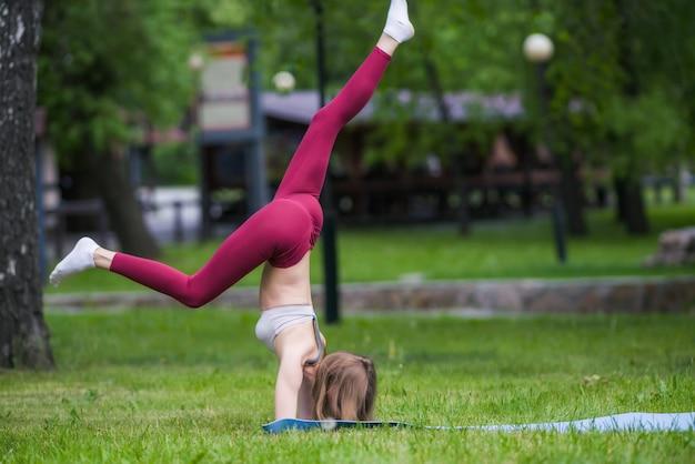 La donna graziosa che fa l'yoga si esercita nel parco