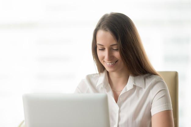 La donna graziosa comunica con gli amici in internet