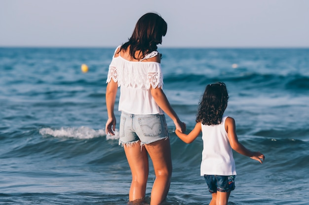La donna graziosa con i jeans corti e sua figlia che posano sull'acqua della spiaggia