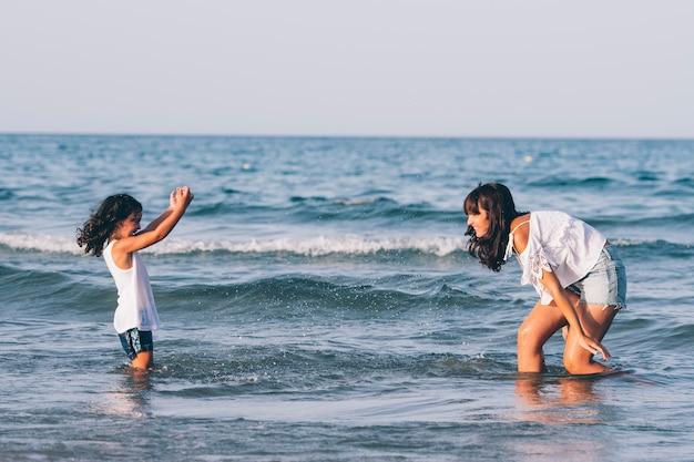 La donna graziosa con le brevi blue jeans e sua figlia che giocano nella spiaggia innaffiano