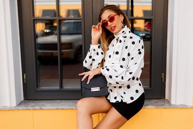 La donna graziosa con le gambe in molla alla moda copre con la piccola borsa che posa sulla via su giallo.
