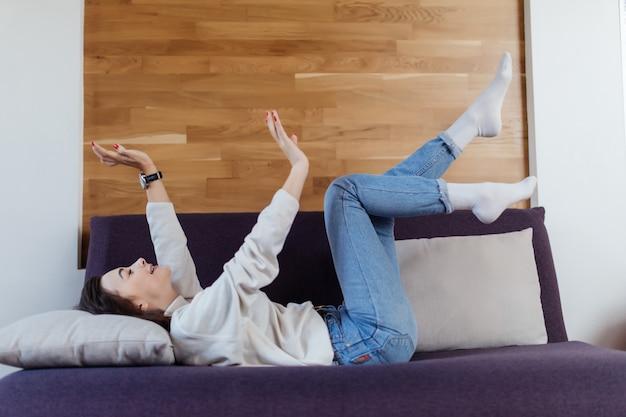 La donna graziosa in maglione e blue jeans bianchi si diverte a cattivo tempo di giorno