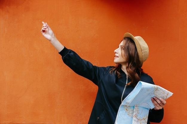 La donna graziosa nel cappello mostra a qualcosa che tiene in sua mappa turistica delle mani