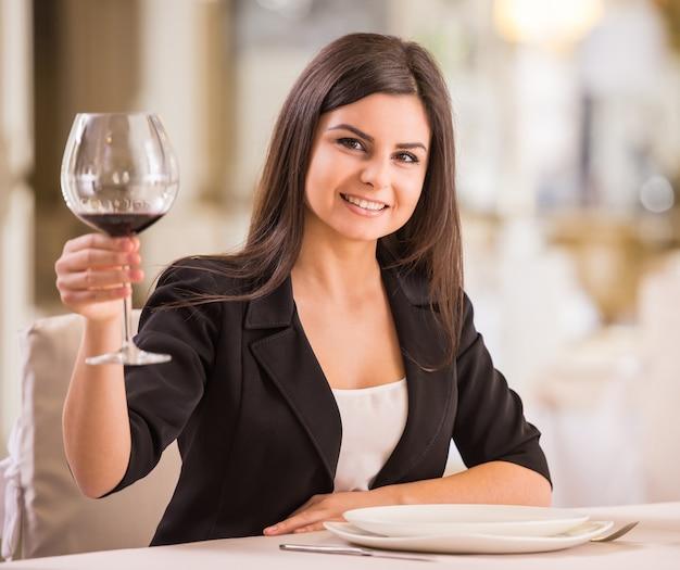 La donna graziosa sta tenendo un bicchiere di vino.