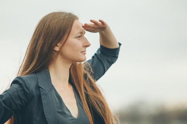 La donna guarda in lontananza. il concetto di manifestazioni di emozioni, problemi di vista.
