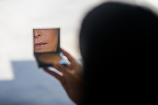 La donna guarda nel piccolo specchio della sua polvere