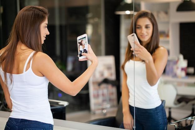 La donna ha fatto il selfie in specchio allo studio di bellezza
