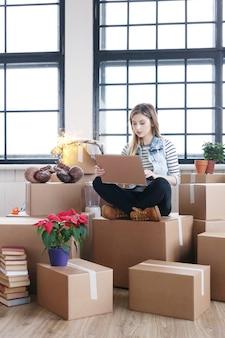 La donna ha finito con i pacchetti di carico e sta chiamando un corriere per la spedizione via computer