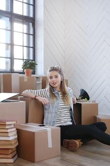 La donna ha finito con i pacchetti di carico ed è seduta sul pavimento in modo soddisfatto