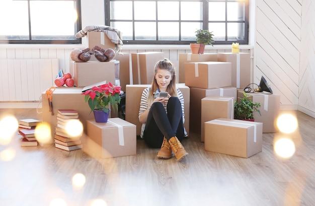 La donna ha finito con i pacchetti di carico ed è seduta sul pavimento mentre chiama un corriere