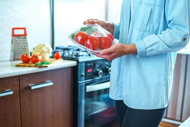 La donna ha imballato gli ortaggi freschi facendo uso del film dell'alimento per conservazione degli alimenti in frigorifero