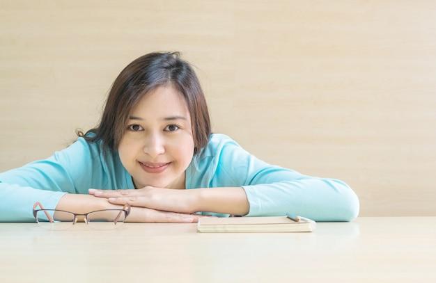 La donna ha mentito sulla scrivania con la faccia felice nel tempo di riposo dalla lettura di un libro