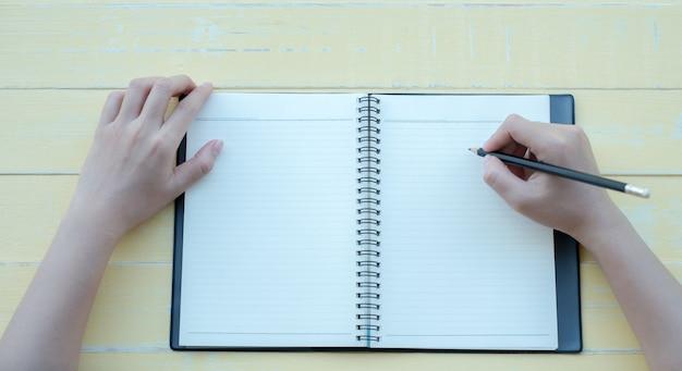 La donna ha scritto il libro con un libro di argilla su uno sfondo giallo. la vista dall'alto
