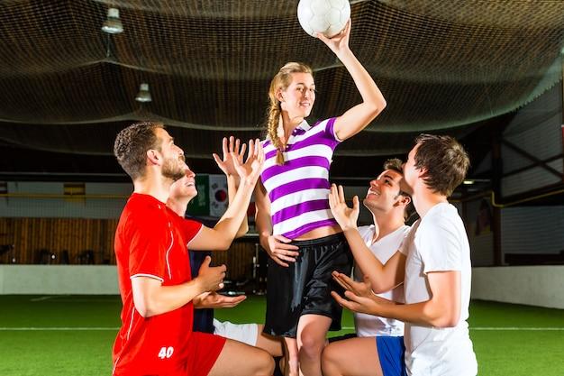 La donna ha un pallone da calcio in mano, gli uomini in ginocchio