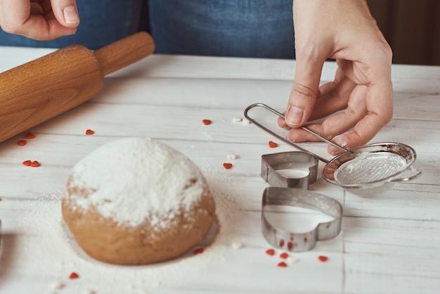 La donna impasta la pasta con le mani in cucina