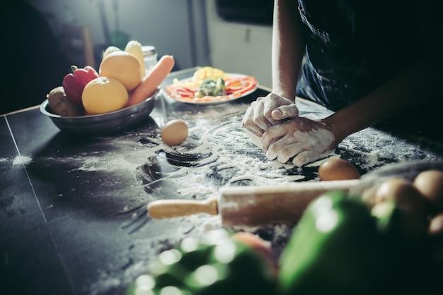 La donna impasta la pasta per fare la pizza su legno. concetto di cottura.