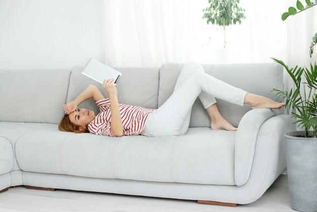 La donna in abiti bianchi comunica tramite collegamento video. chattare online e salutare lo schermo del computer.