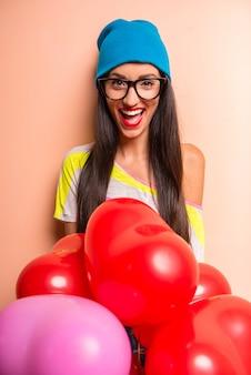 La donna in abiti colorati si diverte con palloncini.