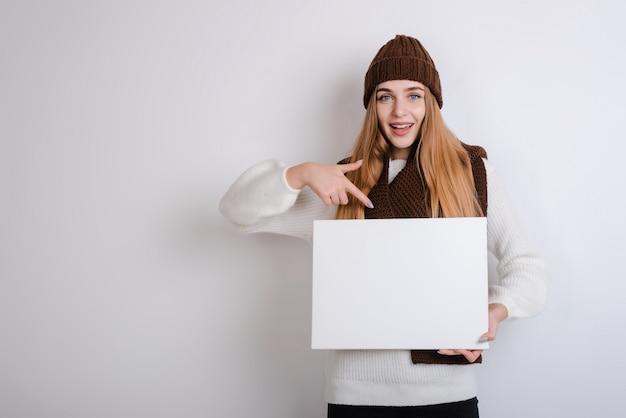 La donna in abiti invernali detiene un poster bianco e punta il dito su uno sfondo grigio