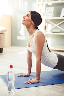 La donna in abiti sportivi sta sorridendo mentre faceva yoga.