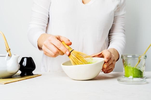 La donna in bianco prepara il tè matcha verde giapponese frullandolo in una ciotola con una frusta chasen di bambù