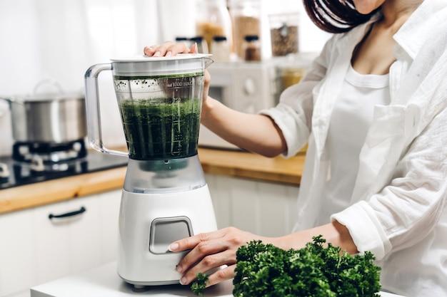 La donna in buona salute gode di fare la pulizia della disintossicazione delle verdure verdi e il frullato della frutta verde con il miscelatore in cucina a casa concetto di dieta stile di vita sano