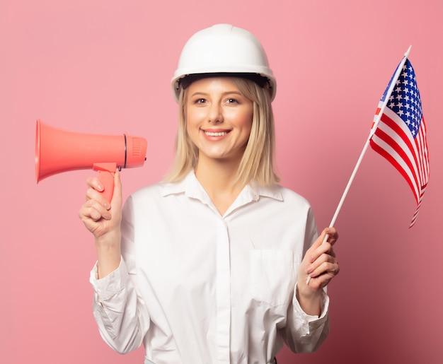 La donna in camicia e casco bianchi tiene l'altoparlante e la bandiera di usa