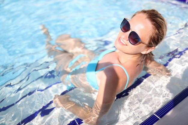 La donna in costume da bagno blu si siede in piscina.