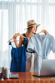 La donna in costume da bagno sceglie abiti, sogna un concetto di vacanza