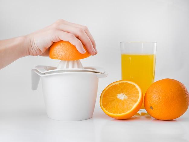 La donna in cucina spreme il succo dell'arancia