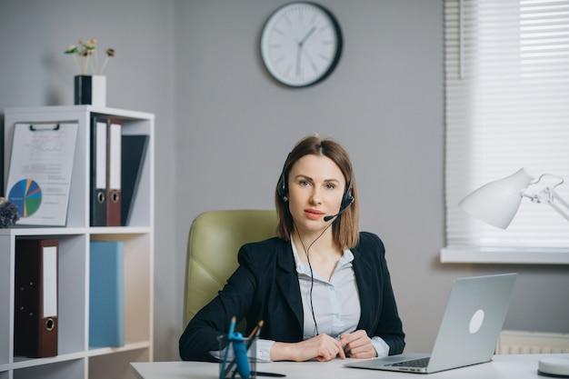 La donna in cuffie che tengono la conversazione di carta del rapporto finanziario alla webcam fa la video chiamata in ufficio