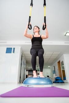 La donna in forma atletica fa esercizio trx
