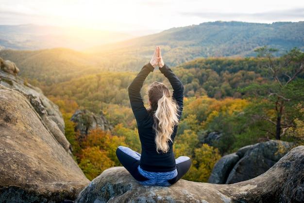 La donna in forma sportiva sta praticando yoga sulla cima della montagna