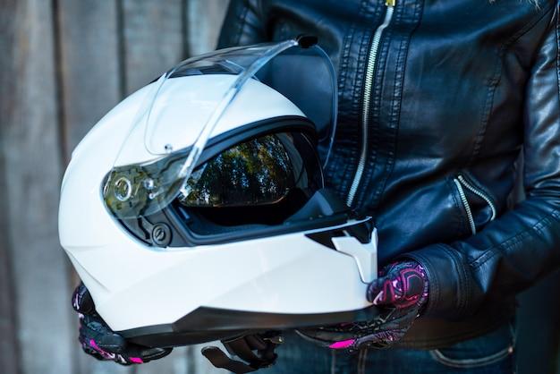 La donna in giacca di pelle tiene il casco da motociclista