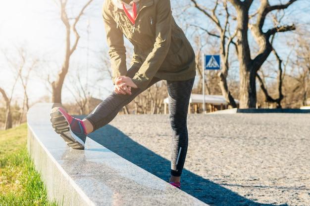 La donna in giacca e scarpe da ginnastica fa esercizi sportivi in un parco al mattino