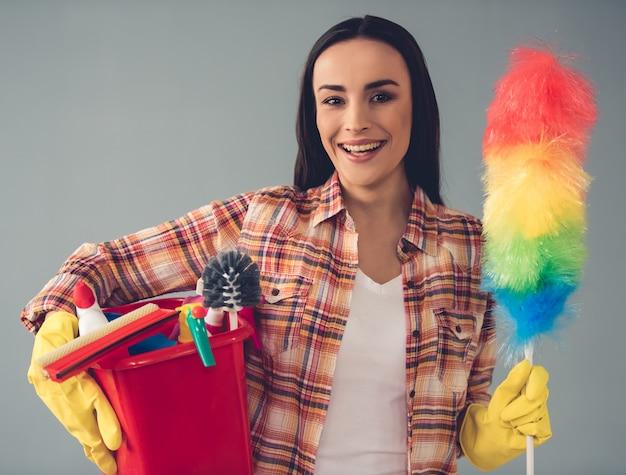 La donna in guanti protettivi sta tenendo uno spolverino statico. concetto di pulizia