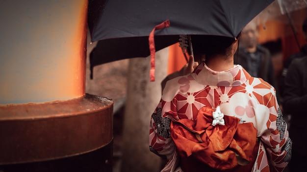 La donna in kimono rosso e l'ombrello in giardino parcheggiano kyoto, giappone