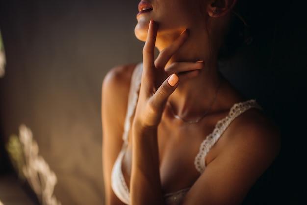 La donna in lingerie bianca tocca il suo collo tenero